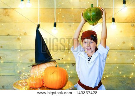 Happy pirate children during Halloween party playing around the table with pumpkins
