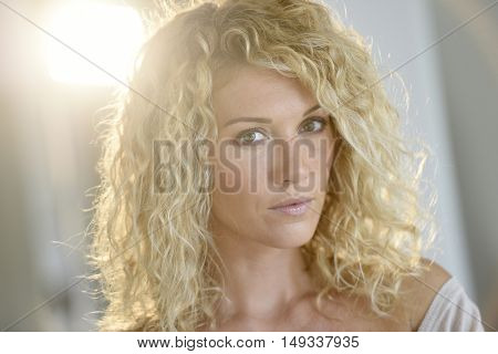 Portrait of attractive woman with long curly hair, isolated