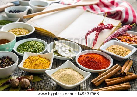 Various spices and blank cookbook on old wooden table.