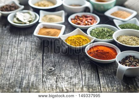 Various dried herbs and spices in ceramic bowls.