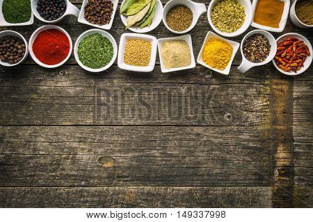 Various dried herbs and spices in ceramic bowls on old wooden table. Top view.