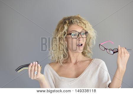 Cheerful woman with curly hair choosing between different eyeglasses