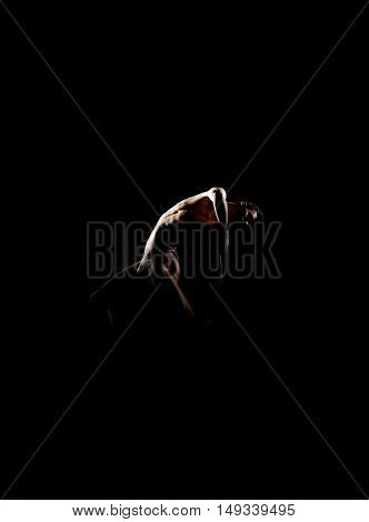 Silhouette trace of male ballet dancer over black background.