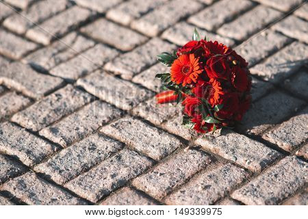 Wedding bouquet on the pavement. Red flowers