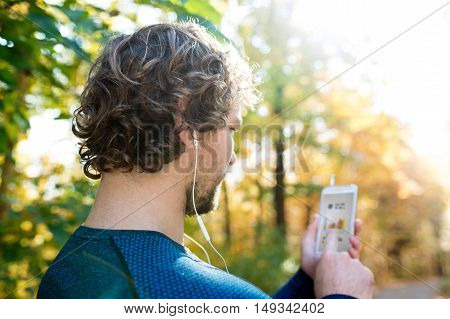 Unrecognizable man running outside in colorful sunny autumn forest using a fitness app on his smartphone. Using phone app for tracking weight loss progress, running goal or summary of his run. Rear view.