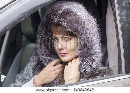 The expressive face of a young pretty girl in the window of the car