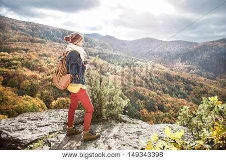 Beautiful woman with backpack, holding binoculars, standing on a rock against colorful autumn forest, rear view