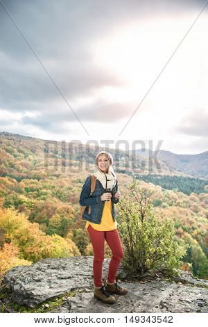 Beautiful woman with backpack, holding binoculars, standing on a rock against colorful autumn forest
