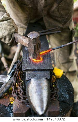 Blacksmith Curves Iron Rod With Hammer On Anvi