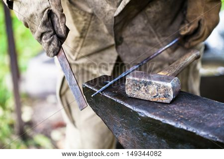 Blacksmith Processing Steel Rod By File On Anvil