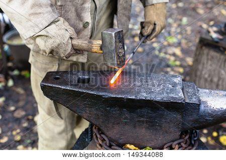 Blacksmith Hammering Hot Steel Rod On Anvil