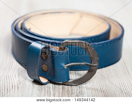 hand made blue leather belt with forged buckle on wooden table