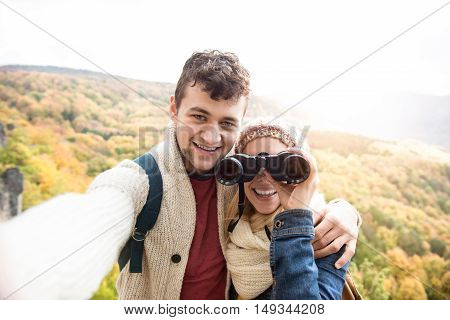Beautiful young couple on a walk in sunny autumn forest taking selfie, woman looking through binoculars