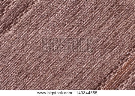Light brown background of a knitted textile material with diagonal pattern. Fabric with a striped texture closeup.