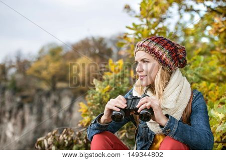 Beautiful young woman holding binoculars against colorful sunny autumn forest