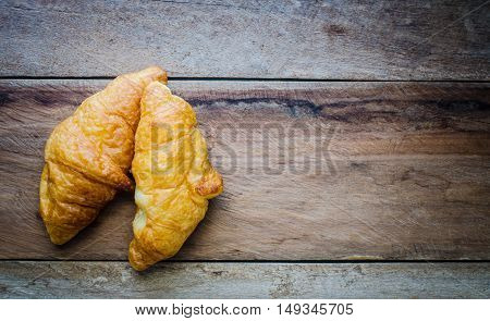 Croissants on plate on wooden table for coffee break