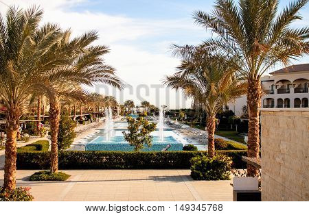 Beautiful view of the hotel in tropical luxury with swimming pool with palm trees on the shore of the Red Sea in Egypt