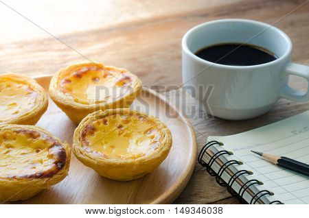 egg tart coffee notebook and pencil on the wooden table - tone vintage