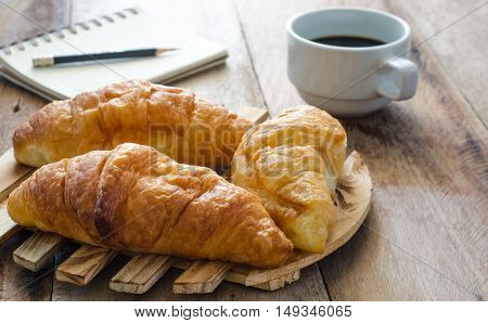 Croissants coffee notebook and pencil on the wooden table - tone vintage