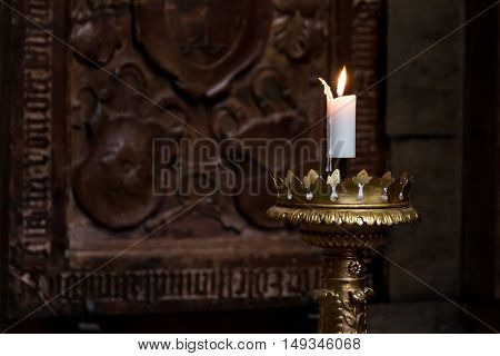 Burning candle on the vintage gold candlestick in St. Vitus Cathedral Prague