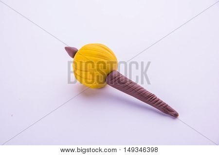 model of gada or gadda favourite weapon of Lord Hanuman made up of play dough or playdough or colourful clay, selective focus isolated over white background
