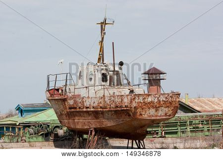 Old fishing boat rusts on the shore