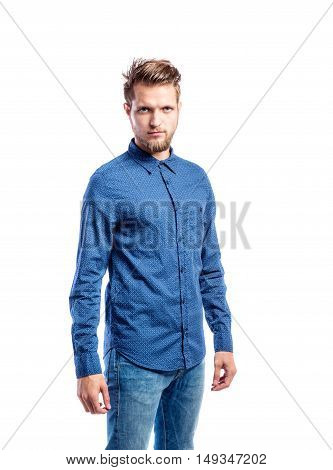 Hipster man in jeans and blue long-sleeved shirt, studio shot on white background, isolated