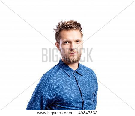 Hipster man in blue long-sleeved shirt, studio shot on white background, isolated