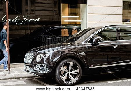 PARIS FRANCE - MAY 21 2016: Man admiring the luxury Bentley Bentayga Hybrid SUV on the streets of Paris France