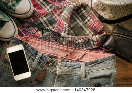 Accessory smart phone jeans Shoeswallet jeans hats shirt on a wooden floor for trip
