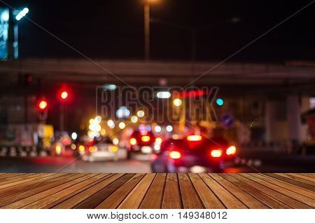 Wooden plank and blurred bokeh image of traffic jam at nightf traffic jam at night