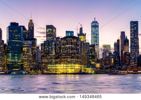 Sunset in New York City with a view of the East River and the  illuminated skyline of Lower Manhattan