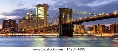 Sunset in New York City with a view of the Brooklyn Bridge illuminated for the night