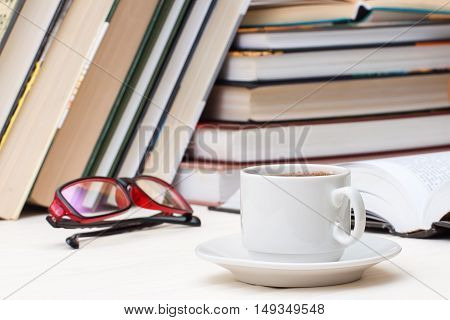 cup of coffee on against the background of the books