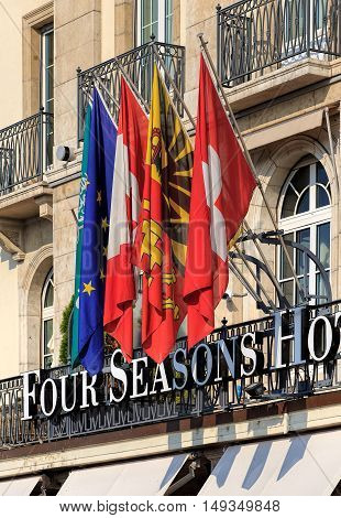 Geneva, Switzerland - 24 September, 2016: flags over the entrance to the Four Seasons Hotel Les Bergues. Hotel Les Bergues has been a landmark on Lake Geneva since 1834.