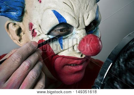 closeup of a young man making up himself as an evil clown, using a mirror