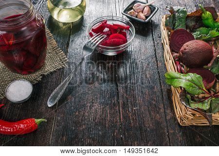 Whole and sliced beetroots on wicker tray and chopped pickled beets of dark wooden table