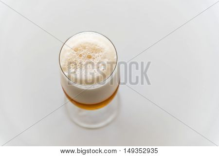 Glass of fresh lager beer on white table