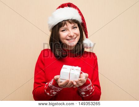 Closeup portrait of Santa girl holding christmas gift. Young happy woman in santa hat showing Christmas present. Beautiful cute young santa woman.