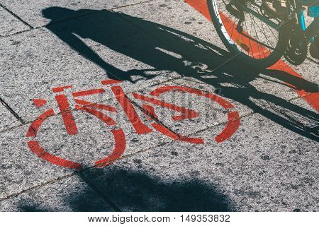 Shadow of female biker riding a bike and bicycle symbol route road marking