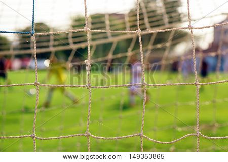 Soccer goal net with players in defocussed background