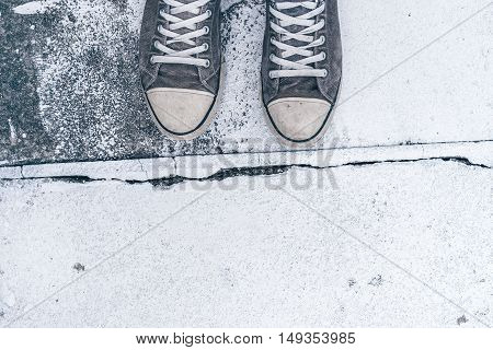 Young man standing on the street top view of worn gray sneakers on concrete floor with crack line as border - concept of obstacles difficulties hardship and restrictions in life.