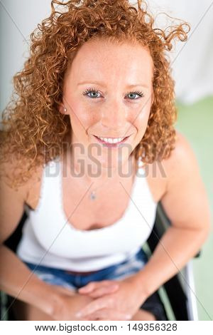 Close up overhead view of woman in wheelchair as she smiles towards the camera