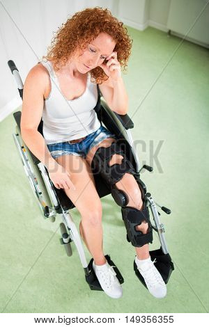 Overhead View Of Sad Woman In Leg Brace And Shorts