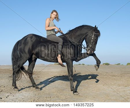 horse woman make dressage with her stallion on the beach