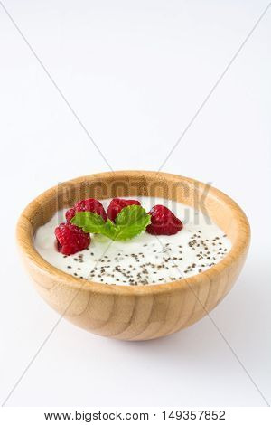 Chia yogurt with raspberries in a wooden bowl isolated on white background