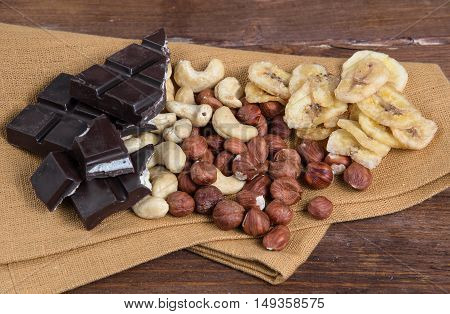 Chocolate and nuts with napkin on a wood