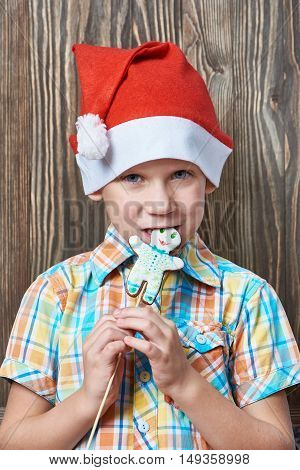 Little Boy In New Year's Red Cap Eats Christmas Cookies