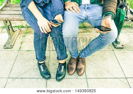 Couple of hipsters holding mobile phone sitting on bench - Two trendy guys using cell at city park - people legs and hands with smartphone outdoors - Modern concept of romance - Vintage filter look