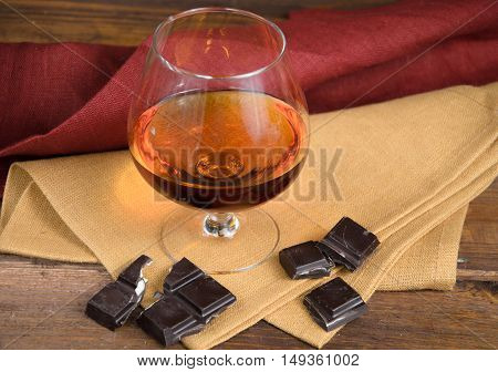Glass of brandy and a chocolate on a old wooden table
